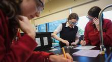 Raissa Dzulynska, Jackie Midroni and Fiona McKay work on an experiment in Grade 12 chemistry at St. Clement's School in Toronto. (JENNIFER ROBERTS)