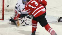 Canada's Caroline Ouellette (13) scores against U.S. goalie Jessie Vetter during the Four Nations Cup women's hockey tournament championship game in Lake Placid, N.Y., Sunday, Nov. 9, 2008. (Todd Bissonette/AP)
