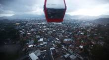 A cable car passes over the Complexo do Alemao pacified 'favela' community on March 23, 2014 in Rio de Janeiro, Brazil. The 'favela' was previously controlled by drug traffickers and is now occupied by the city's Police Pacification Unit (UPP). A number of UPP's were attacked by drug gang members on March 20 and some pacified favelas will soon receive federal forces as reinforcements. The UPP are patrolling some of Rio's favelas amid the city's efforts to improve security ahead of the 2014 FIFA World Cup and 2016 Olympic Games. Mario Tama/Getty Images