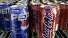 Cans of Pepsi and Coke are shown in a news stand refrigerator display rack in a New York file photo from April 22, 2005. (MARK LENNIHAN/AP)