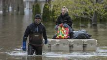 Olivier St-Denis pulls Marie-Pierre Chalifoux through the flooded streets of Saint-André-d'Argenteuil, Que., on Tuesday. (Dario Ayala/the globe and mail)