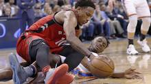 DeMar DeRozan and Thunder forward Jerami Grant scramble for a loose ball during the second half. (Alonzo Adams/AP)