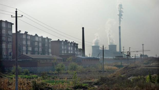 A coal-fired power plant looms behind apartments in Tangshan, China. Greenpeace has estimated that particles from a single coal-fired power plant can drift 1,000 kilometres. (The Globe and Mail)