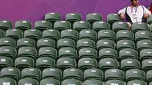 A spectator sits amid empty seats during the women's singles match between Denmark's Caroline Wozniacki and Great Britain's Anne Keothavong at the London 2012 Olympics Games on July 28, 2012. (STEFAN WERMUTH/REUTERS)