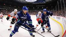 Vancouver Canucks forward Henrik Sedin (33) and forward Jannik Hansen (36) move to the boards against Calgary Flames defenceman T.J. Brodie (7) and forward Sean Monahan (23) during the first period at Rogers Arena. (Anne-Marie Sorvin/USA Today Sports)
