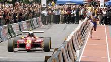 Someone had the right idea back in 2002 when Canadian track-and-field Olympic gold medalist Bruny Surin raced a Formula Atlantic car driven by Stephane Roy in downtown Montreal. (Timothy Clary/AFP)