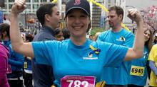 Liberal Leader Christy Clark strikes a pose in the start area of the Vancouver Sun Run in downtown Vancouver, April 21, 2013. (Jonathan Hayward/The Canadian Press)