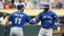 Toronto Blue Jays third baseman Josh Donaldson is congratulated by Kevin Pillar after he hit a two-run home run in the 10th inning against the Oakland Athletics at Oakland Alameda Coliseum on June 7, 2017. (Ezra Shaw/Getty Images)