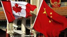 Canadian and Chinese national flags hang from a lamp post in front of the giant portrait of former Chinese Chairman Mao Zedong at Beijing's Tiananmen Square December 2, 2009. Charges of smuggling against a Canadian winery owner who has been locked up in a Chinese jail for more than a year are trumped up, his lawyers say, (DAVID GRAY/REUTERS)