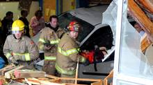 Rescue workers respond to a scene where a vehicle crashed into a Racette School classroom in St. Paul, Alberta, Thursday, October 25, 2010. (RYAN McCRACKEN/ST. PAUL JOURNAL)
