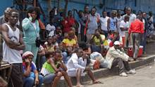 People wait for Liberian security forces to allow them to deliver foodstuff to friends and family members in the West Point area that has been hardest hit by the Ebola virus spreading in Monrovia, Liberia, Monday, Aug. 25, 2014. (Abbas Dulleh/AP)