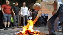 People burn copies of emergency tax notices Friday outside a tax office in the northern Greek port city of Thessaloniki. AP Photo/Nikolas Giakoumidis (Nikolas Giakoumidis/AP)