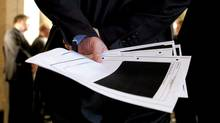 Liberal MP Bob Rae holds blacked-out detainee-related pages released by the government. (Sean Kilpatrick/The Canadian Press)