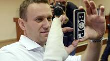 "Russian opposition leader Alexei Navalny holds a smartphone with an ironic sign that reads: ""Thief's taking pictures after a trial"" in Kirov, Russia, in, April, 2013.. (AP Photo/Mitya Aleshkovskiy) (Mitya Aleshkovskiy/AP)"