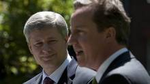 Canadian Prime Minister Stephen Harper listens to British Prime Minister David Cameron during a joint news conference in the gardens at 10 Downing Street in London, Thursday June 3, 2010. (Adrian Wyld/Adrian Wyld/The Canadian Press)