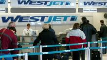 File photo of passengers lining up at a WestJet counter at the Winnipeg Airport. (Wayne Glowacki/CP)