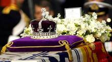 "The Koh-i-noor, or ""mountain of light,"" diamond, set in the Maltese Cross at the front of the crown made for Britain's late Queen Mother Elizabeth, is seen on her coffin, along with her personal standard, a wreath and a note from her daughter, Queen Elizabeth II, as it is drawn to London's Westminster Hall in this April 5, 2002 file photo. (ALASTAIR GRANT/AP)"