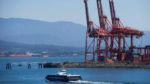 A SeaBus passenger ferry passes cargo cranes at port while crossing Burrard Inlet to North Vancouver after leaving Waterfront Station in Vancouver on July 2, 2015. (DARRYL DYCK/THE CANADIAN PRESS)