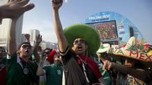 A Mexico soccer fan cheers before his team's World Cup match with Brazil inside the FIFA Fan Fest area on Copacabana beach in Rio de Janeiro, Brazil, Tuesday, June 17, 2014. (Silvia Izquierdo/AP)