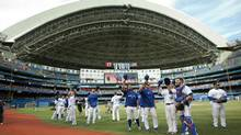 On the last day of the season Toronto Blue Jays players come out of the dugout to tip their hats to fans. The Jays finished with one more win this season that last season. (FRED THORNHILL/REUTERS)