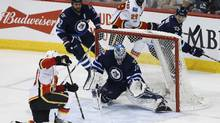 Winnipeg Jets goalie Connor Hellebuyck saves the shot from Calgary Flames' Mikael Backlund during action in Winnipeg on Saturday, March 11, 2017. (JOHN WOODS/THE CANADIAN PRESS)