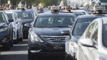 Taxi cabs block a Montreal street during a demonstration against Uber on Oct. 5, 2016. (Graham Hughes/THE CANADIAN PRESS)