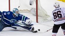 Chicago Blackhawks' Teuvo Teravainen, right, scores against Vancouver Canucks' goalie Ryan Miller during the third period of an NHL hockey game in Vancouver, B.C., on Sunday March 27, 2016. (DARRYL DYCK/THE CANADIAN PRESS)