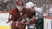 Phoenix Coyotes defenseman David Schlemko, left, checks Los Angeles Kings centre Mike Richards, right, as they chase down a loose puck in the first period of an NHL hockey game Tuesday, April 2, 2013, in Glendale, Ariz. (Associated Press)