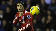 Liverpool's Luis Suarez throws the ball during their English Premier League soccer match against Wigan Athletic in Wigan, northern England December 21, 2011. (Reuters)