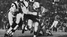 FILE - In this Sept. 4, 1971 file photo, Los Angeles Ram's Deacon Jones, centre, knocks the ball loose from San Diego Chargers' Mike Garrett in Los Angeles. Jones, the original sackmaster, has died. The Hall of Fame defensive end credited with terming the word sack for how he knocked down quarterbacks, was 74. The Washington Redskins said that Jones died of natural causes at his home in Southern California on Monday night, June 3, 2013. (AP)