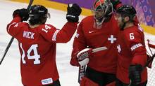 Switzerland's goalie Jonas Hiller (C) celebrates with teammates Roman Wick (L) and Yannick Weber after they defeated the Czech Republic in their men's preliminary round ice hockey game at the 2014 Sochi Winter Olympic Games, February 15, 2014. (GRIGORY DUKOR/REUTERS)