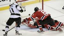 Los Angeles Kings' Kopitar scores on New Jersey Devils goalie Brodeur as Devils' Zubrus tries to cover the play during overtime in Game 1 of the Stanley Cup final in Newark (RAY STUBBLEBINE/Ray Stubblebine/Reuters)