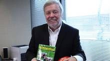 Hugh Heron in his office with a book about the Celtics and a souvenir soccer ball