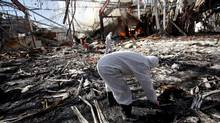 Forensic experts investigate the scene at the community hall where Saudi-led warplanes struck a funeral in Sanaa, the capital of Yemen, on Saturday. (KHALED ABDULLAH/REUTERS)