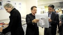 Bob Geldof looks over some front-page designs as Bono chats with Globe and Mail editor-in-chief John Stackhouse. (Kevin Van Paassen/The Globe and Mail)