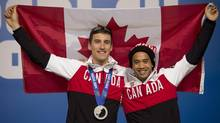 Canadian speed skaters Denny Morrison and Gilmore Junio hold up a Canadian flag following a news conference at the Sochi Winter Olympics Sunday February 16, 2014 in Sochi, Russia. (Adrian Wyld/THE CANADIAN PRESS)
