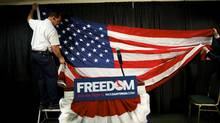 Workers hang a U.S. flag as the backdrop for conservative Rick Santorum's stage before his announcement that he is dropping out of the Republican presidential race in Gettysburg, Pa., April 10, 2012. (MARK MAKELA/REUTERS/MARK MAKELA/REUTERS)