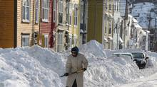 A woman shovels out after a winter storm hit St. John's. Nfld., on Jan.5, 2014. The province's schools are closed until Wednesday. (Paul Daly/The Canadian Press)