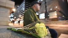 A member of the Canadian Forces (naval) came down to lay flowers for the slain Forces member who was shot on duty at the Canadian War Memorial in Ottawa on Oct 22 2014. Much of downtown Ottawa was shutdown after a gunmen shot and skilled a member of the Canadian Forces who was staring guard at the War Memorial near Parliament Hill. The gunman then made his way to Parliament Hill where he gained entry and began shooting. The shooter was taken down by Hill security forces on Oct 22 2014. (Fred Lum/The Globe and Mail)