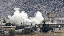 Smoke, caused by mortar bombs and gunfire during clashes between the Syrian Army and rebels, rises from the Syrian border town of Azmarin as seen from the Turkish-Syrian border near the village of Hacipasa in Hatay province October 11, 2012. (OSMAN ORSAL/REUTERS)
