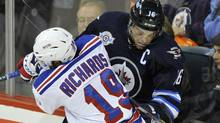 New York Rangers' Brad Richards (19) checks Winnipeg Jets' Andrew Ladd into the boards during the first period of their NHL game in Winnipeg, October 24, 2011. (FRED GREENSLADE/REUTERS)