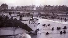 Canadian troops wade ashore after landing in the D-Day invasion at Bernieres-sur-Mer in this June 6, 1944 handout photo. Hundreds of veterans are gathering on June 2009 in Normandy to commemorate the 65th anniversary of the D-Day invasion. The building now known as Queen's Own Rifles House is at left. (HO)