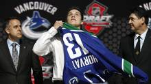 Bo Horvat tries on his Vancouver Canucks jersey after being selected by the Canucks as the ninth overall pick in the 2013 National Hockey league (NHL) draft in Newark, New Jersey, June 30, 2013. (BRENDAN MCDERMID/REUTERS)