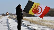 Demonstrator Black Cloud blocks the Canadian National Railway line just west of Portage la Prairie, Manitoba January 16, 2013 as part of the 'Idle No More' movement. The 'Idle No More' movement started in December to protest federal omnibus bills and other legislation aboriginal people say erodes treaty rights. (Fred Greenslade/Reuters)
