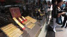 Customers look at gold bars in the window of a shop in Hefei, east China's Anhui province, last April. Gold demand in China, the world's No.1 producer, has exploded in recent years on the back of robust economic growth. (AFP/AFP/GETTY IMAGES)