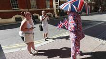 A royal supporter and an onlooker laugh as they stand opposite the Lindo Wing of St Mary's Hospital, where Britain's Catherine, Duchess of Cambridge is due to give birth, in London on July 19, 2013. (SUZANNE PLUNKETT/REUTERS)