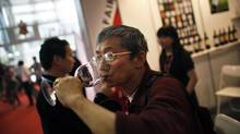A man drinks red wine during the 6th Shanghai International Wine Trade Fair June 1, 2011. (© Carlos Barria / Reuters/REUTERS)