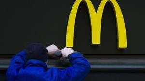 A worker drills a hole underneath the McDonald's brand sign at a store of the global fast-food chain in Berlin in this February 15, 2012 file photograph.