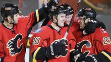 Calgary Flames' Curtis Glencross (20) is congratulated by teammates Mark Giordano, Matt Stajan and Lee Stempniak on the second of Glencross' three goals against Nashville Predators during the third period of their NHL hockey game in Calgary, Alberta, March 15, 2013. (STRINGER/CANADA/REUTERS)