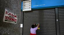 A woman places a leaflet at the entrance of a closed branch of the Hellenic Postbank during a 24-hour general strike on June 28, 2011. Greece ground to a halt on June 28 as a 48-hour general strike began to bite against the bankruptcy-threatened government which is desperately trying to push through sweeping austerity cuts. AFP PHOTO /Alkis Konstantinidis (Photo credit should read Alkis Konstantinidis/AFP/Getty Images) (Alkis Konstantinidis/AFP/Getty Images/Alkis Konstantinidis/AFP/Getty Images)